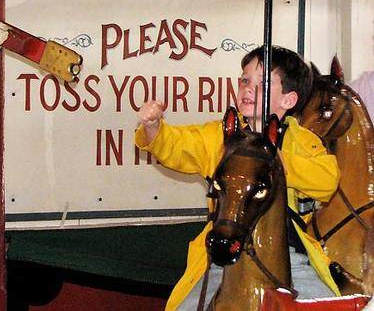Boy reaching for the 'Brass Ring' while riding a Merry-Go-Round.