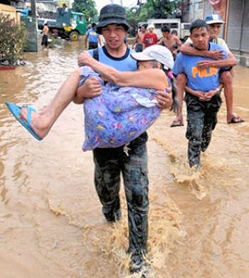 Two men cary an elderly woman and elderly man to safety from a flood.